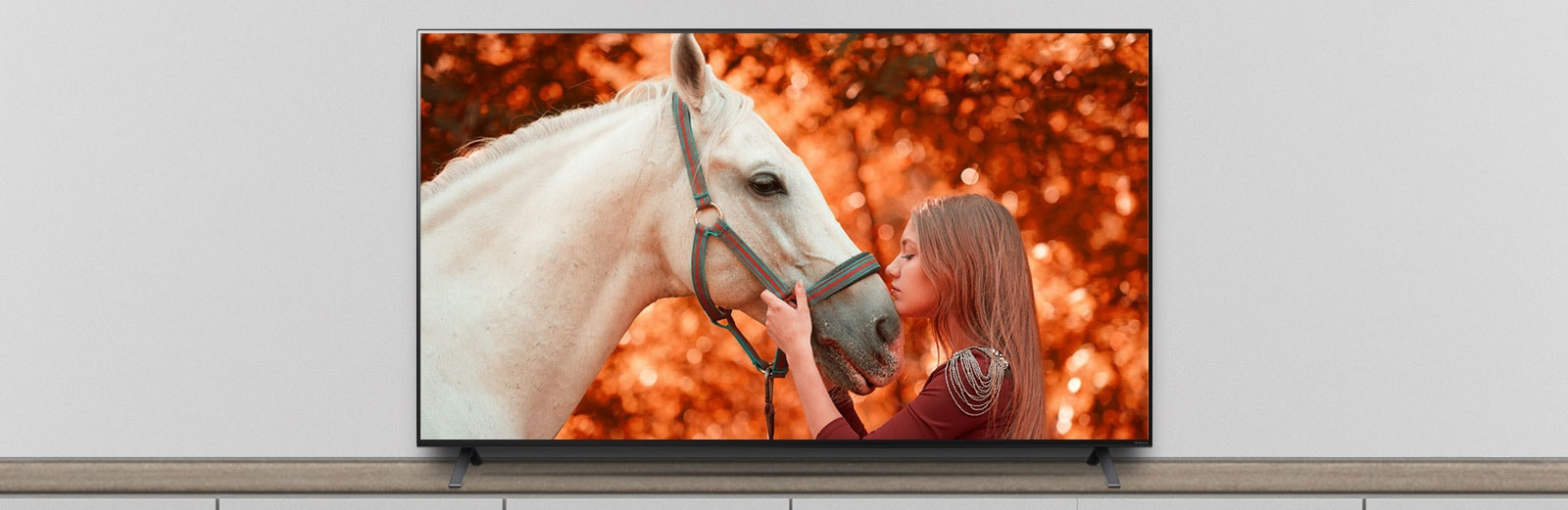 The TV is on the stand, and the screen shows a scene of a movie featuring a horse and a woman.