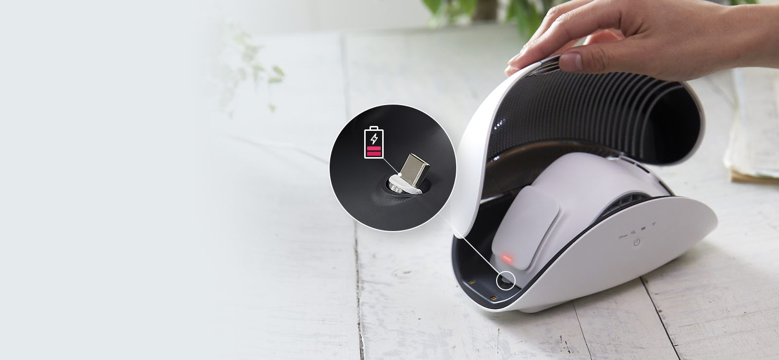 A hand holds open the lid of the purifier case to show the LG PuriCare Wearable Air Purifier sitting inside. There is a red light on the side of the wearable air purifier inside and inset image in a circle with a line to the side of the mask shows a magnified view of the place to recharge the mask. There is also a battery icon that is red and almost empty indicating it's time to plug it in.