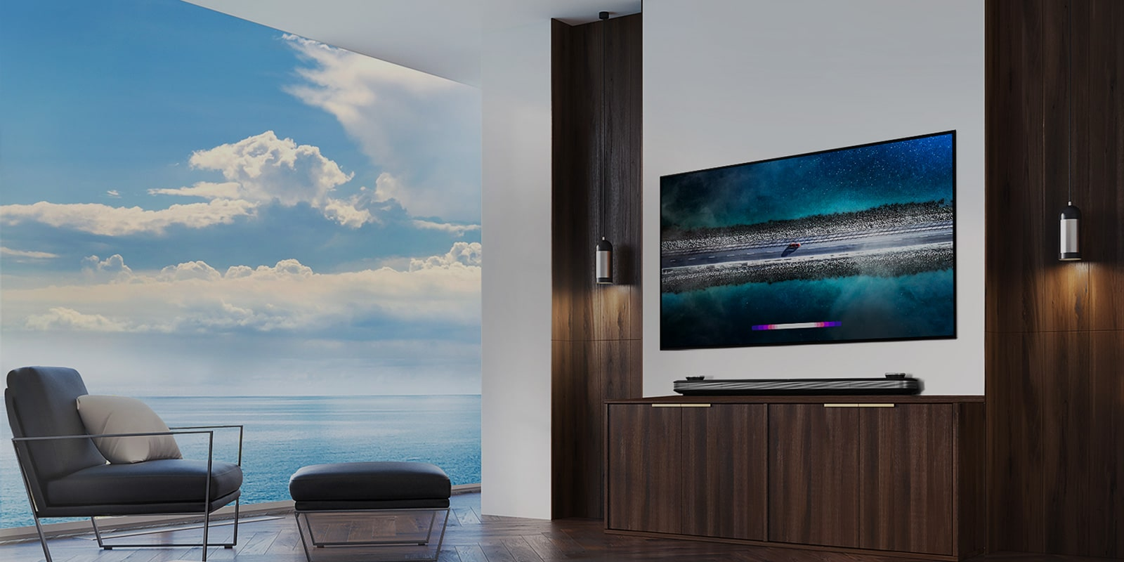 LG SIGNATURE OLED TV W9 is hung on the wall and a counch is laid right in front of tv with the blue sky over the window.