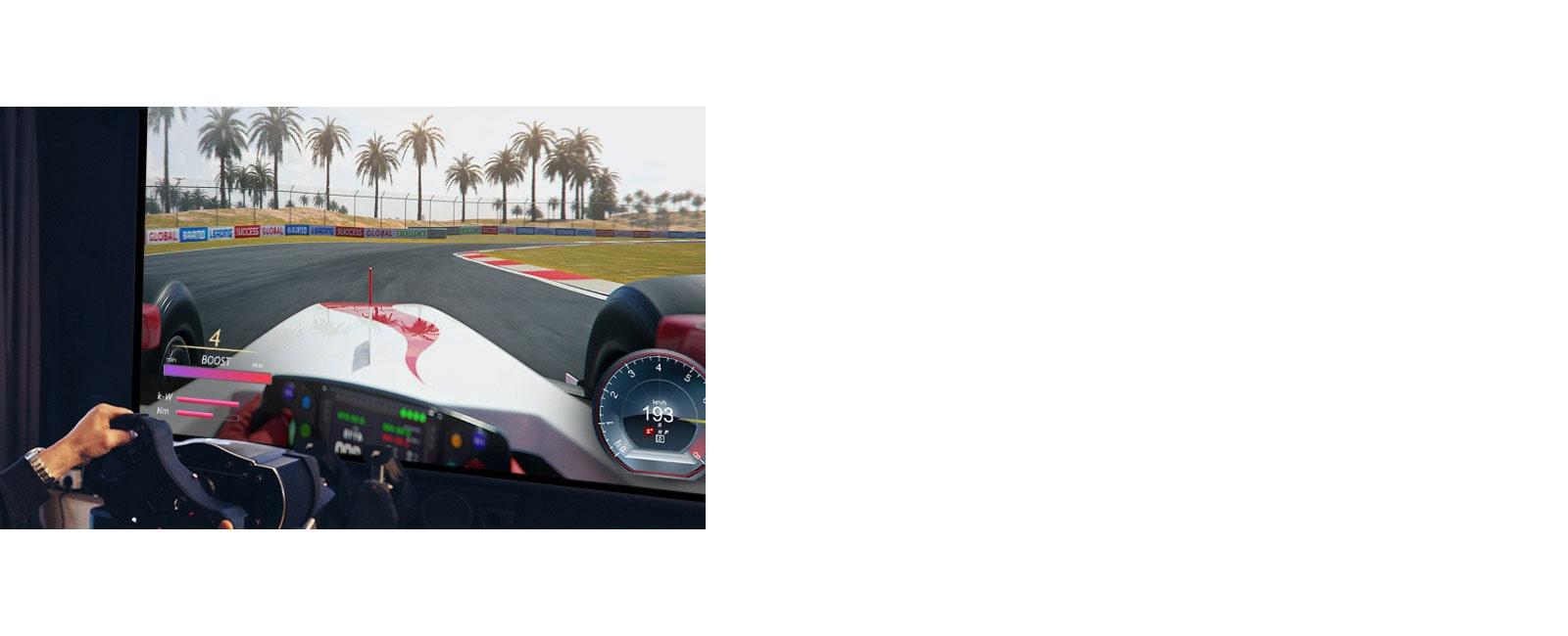 صورة مقربة للاعب يحمل عجلة سباق في إحدى ألعاب السباقات على شاشة التلفزيون.