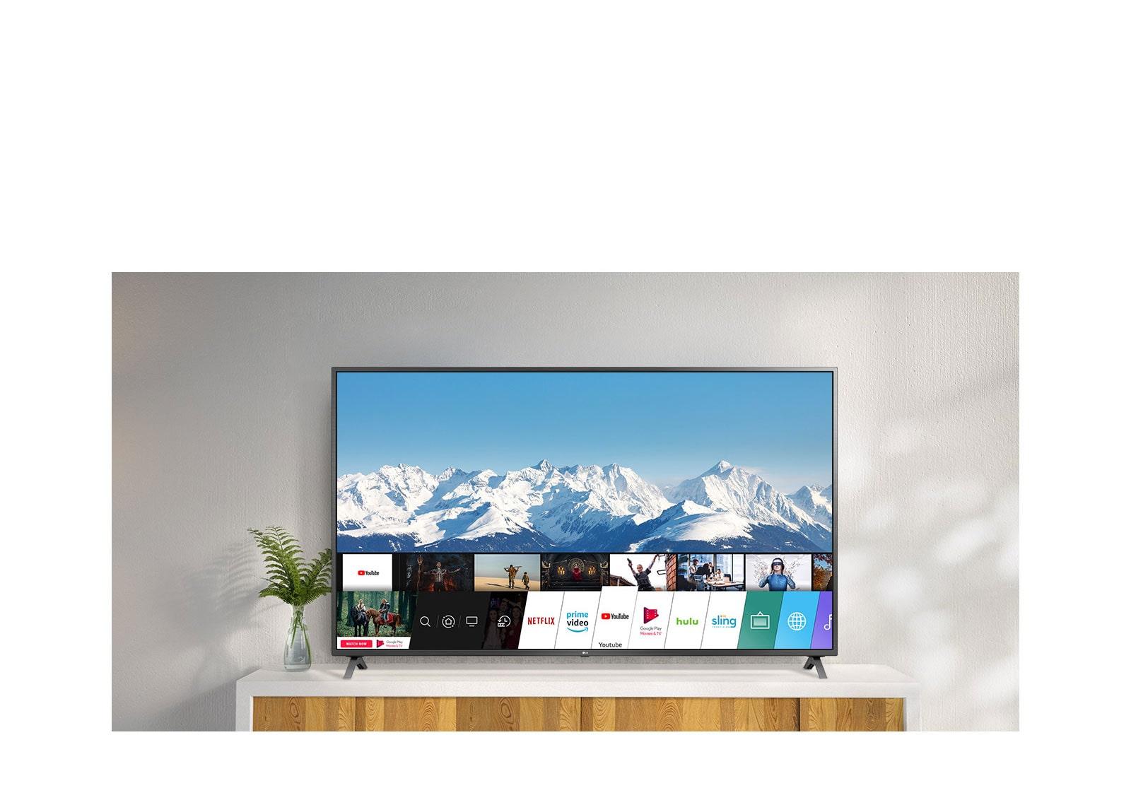 تلفزيون على حامل أبيض مقابل أحد الجدران البيضاء. شاشة تلفزيون تظهر الشاشة الرئيسية مع نظام webOS.