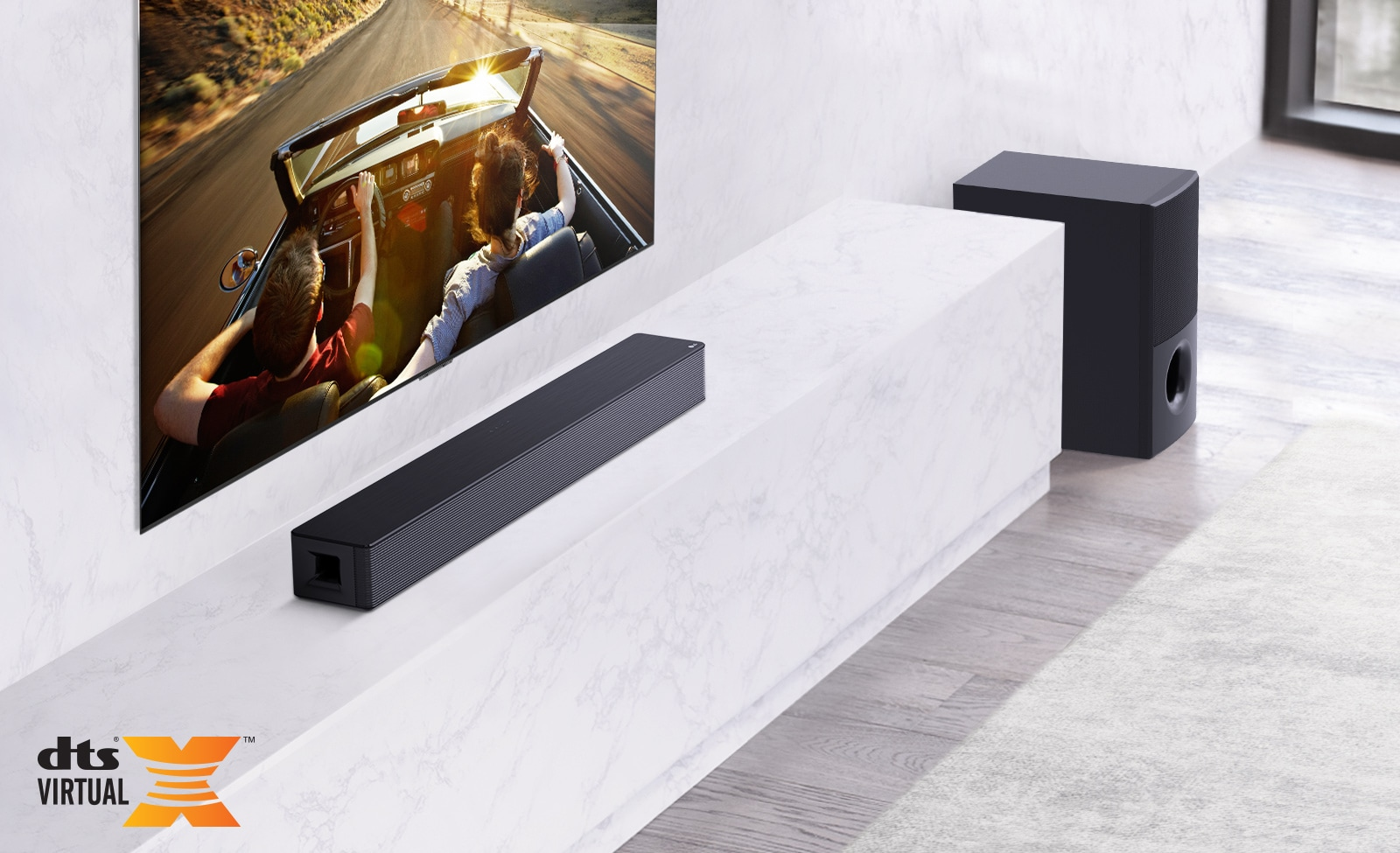 TV is on the wall, LG Soundbar is below on a white marble shelf with a sub-woofer to the right. TV shows a couple in a car.