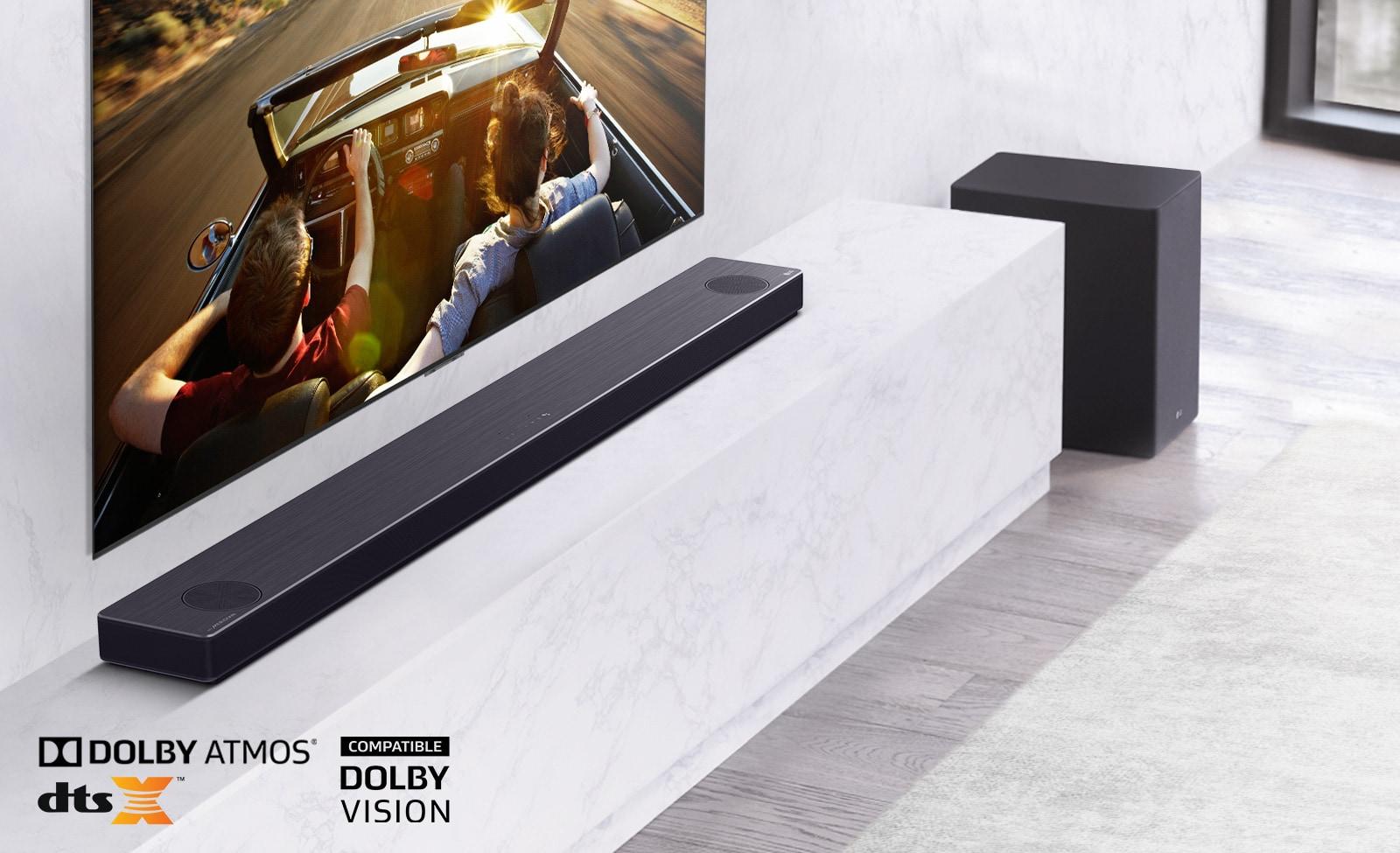 Der Fernseher hängt an der Wand, die LG Sound Bar steht unten auf einem Regal aus weißem Marmor mit einem Subwoofer auf der rechten Seite. Der Fernseher zeigt ein Paar in einem Auto.
