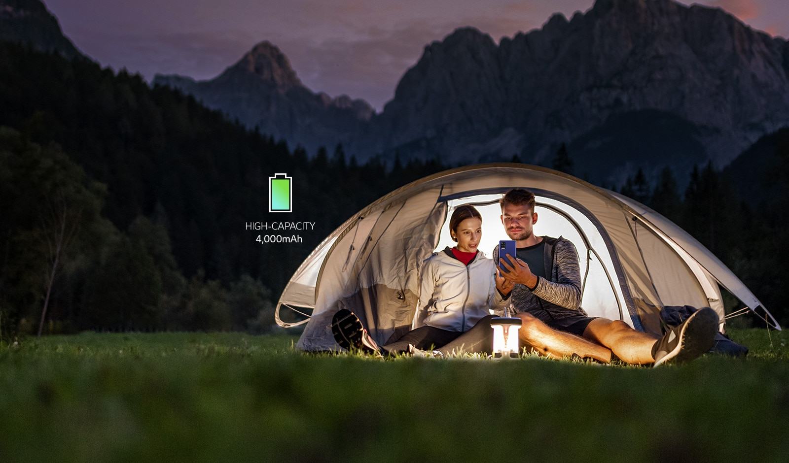 A man and a woman watching a smartphone in a tent in the dark night.