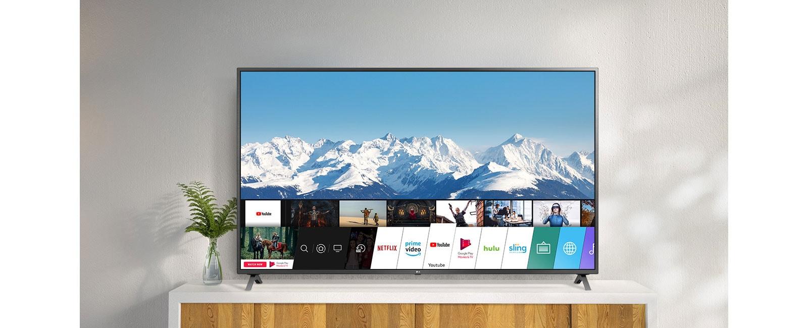 Телевизор, поставен на бяла стойка пред бяла стена. Телевизионен екран, показващ начален екран с webOS.