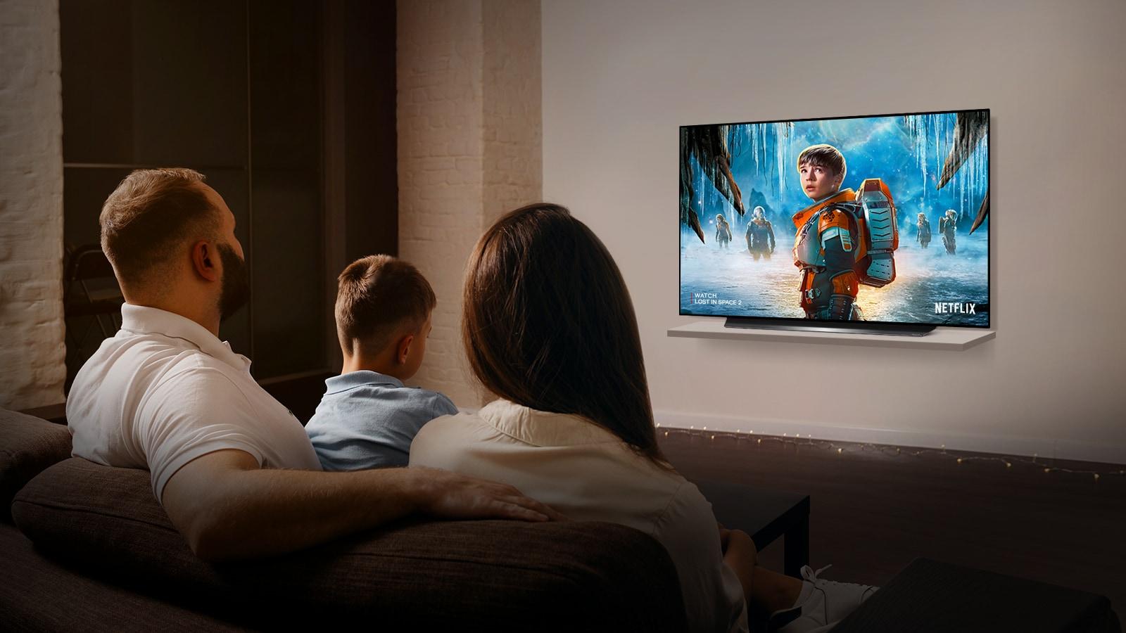 Um casal sentado em um sofá na sala de estar assistindo à série PERDIDOS NO ESPAÇO 2 na TV