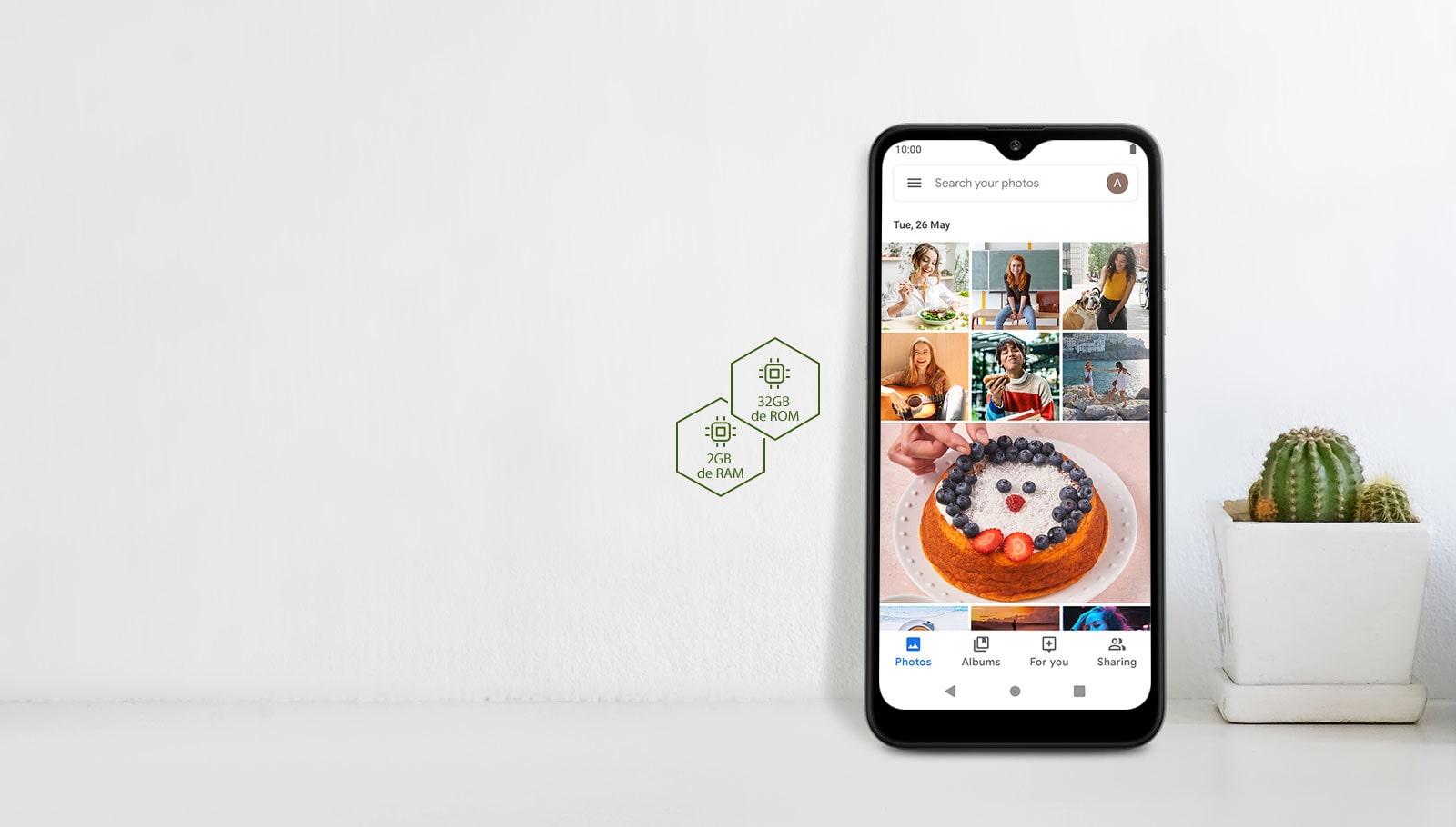 Smartphone com rede social na tela, ao lado de um cacto