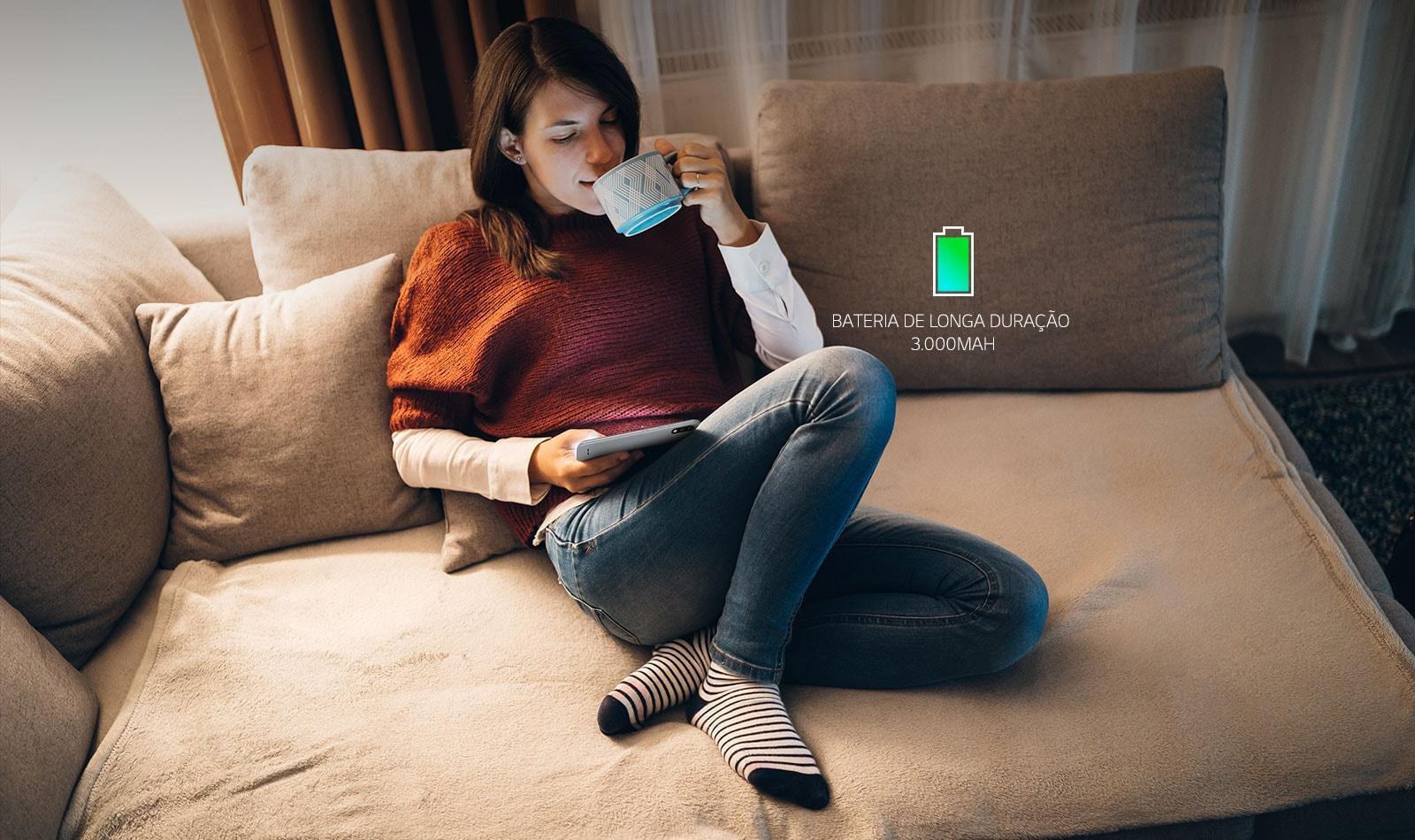 Mulher sentada em um sofá, tomando café e olhando o seu smartphone