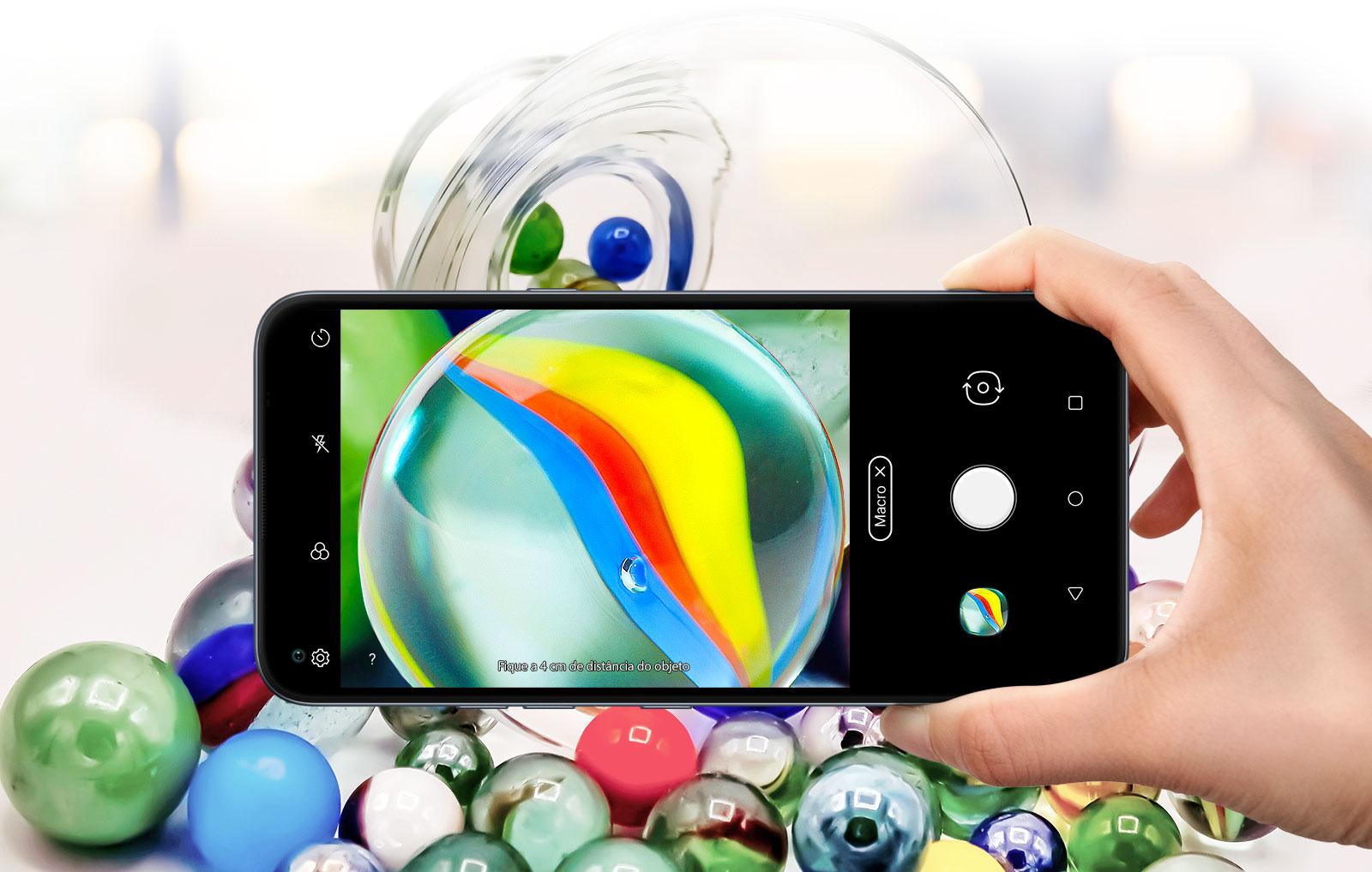Close de alguém segurando um smartphone e fotografando bolas de gude