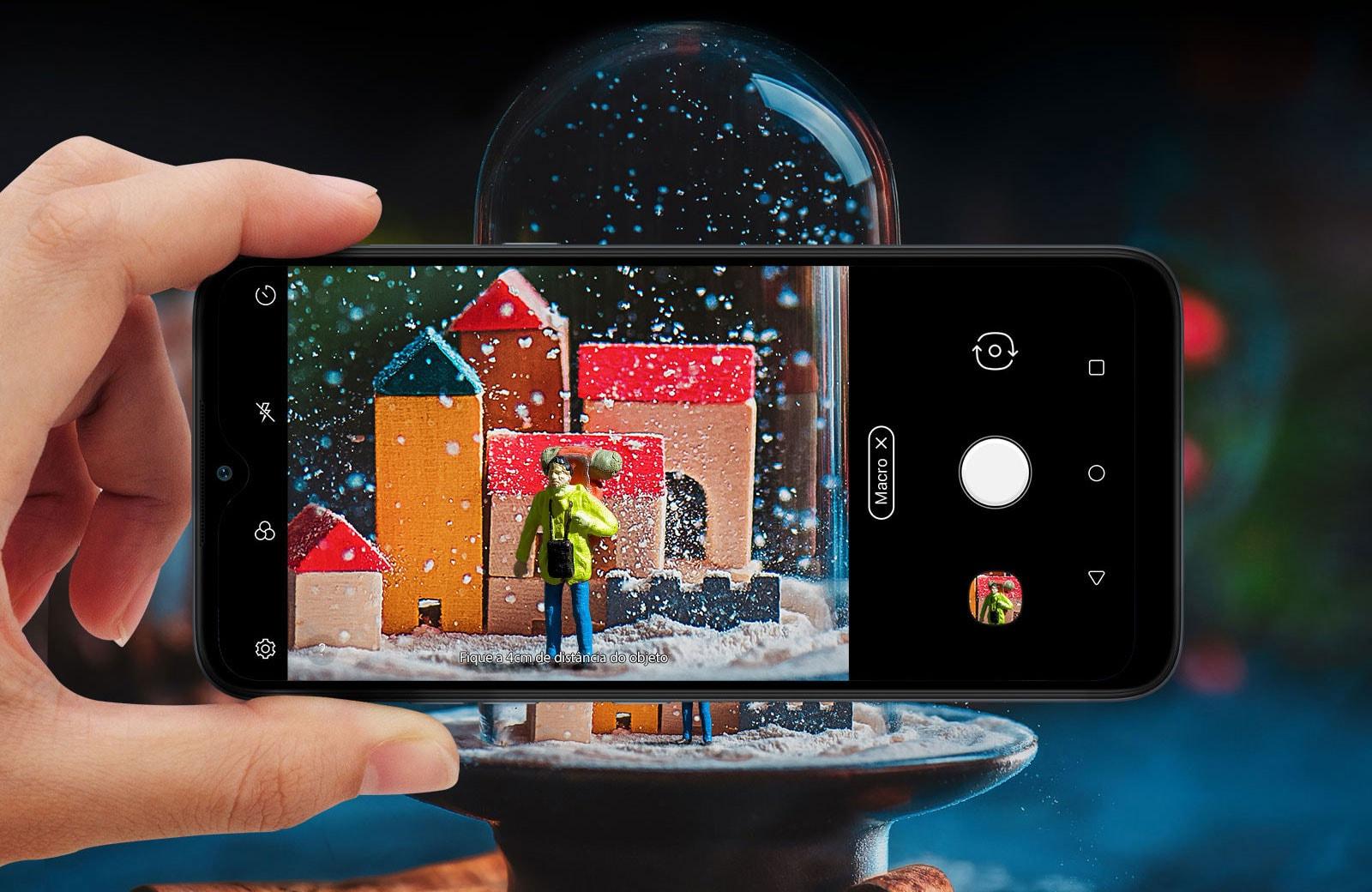 Close de alguém segurando um smartphone e fotografando uma bola de neve