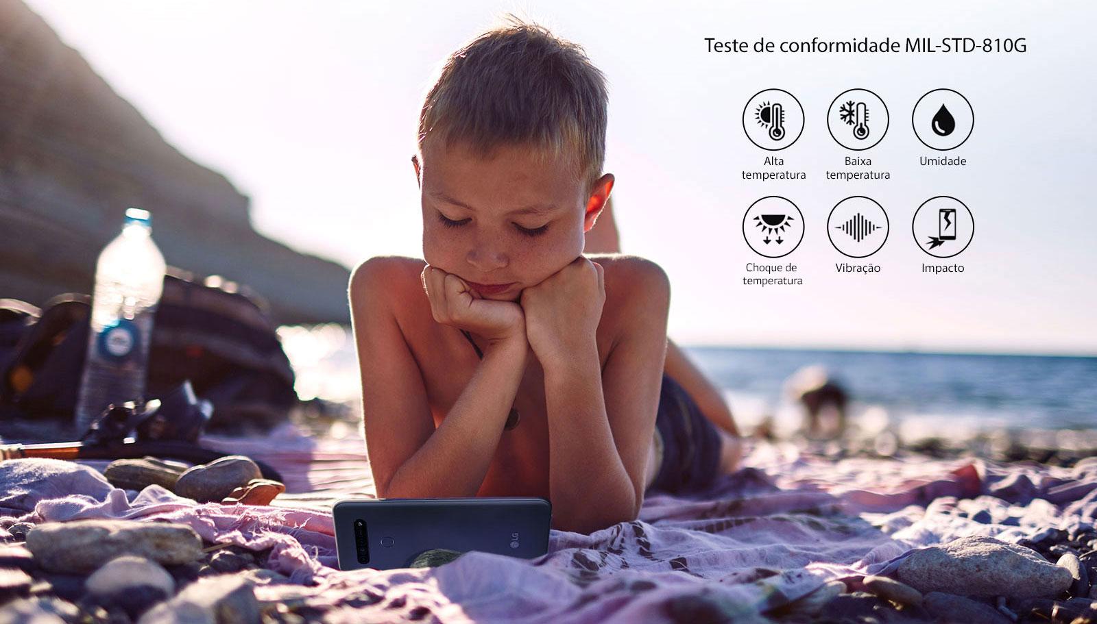 Menino deitado na praia assistindo a um filme no smartphone