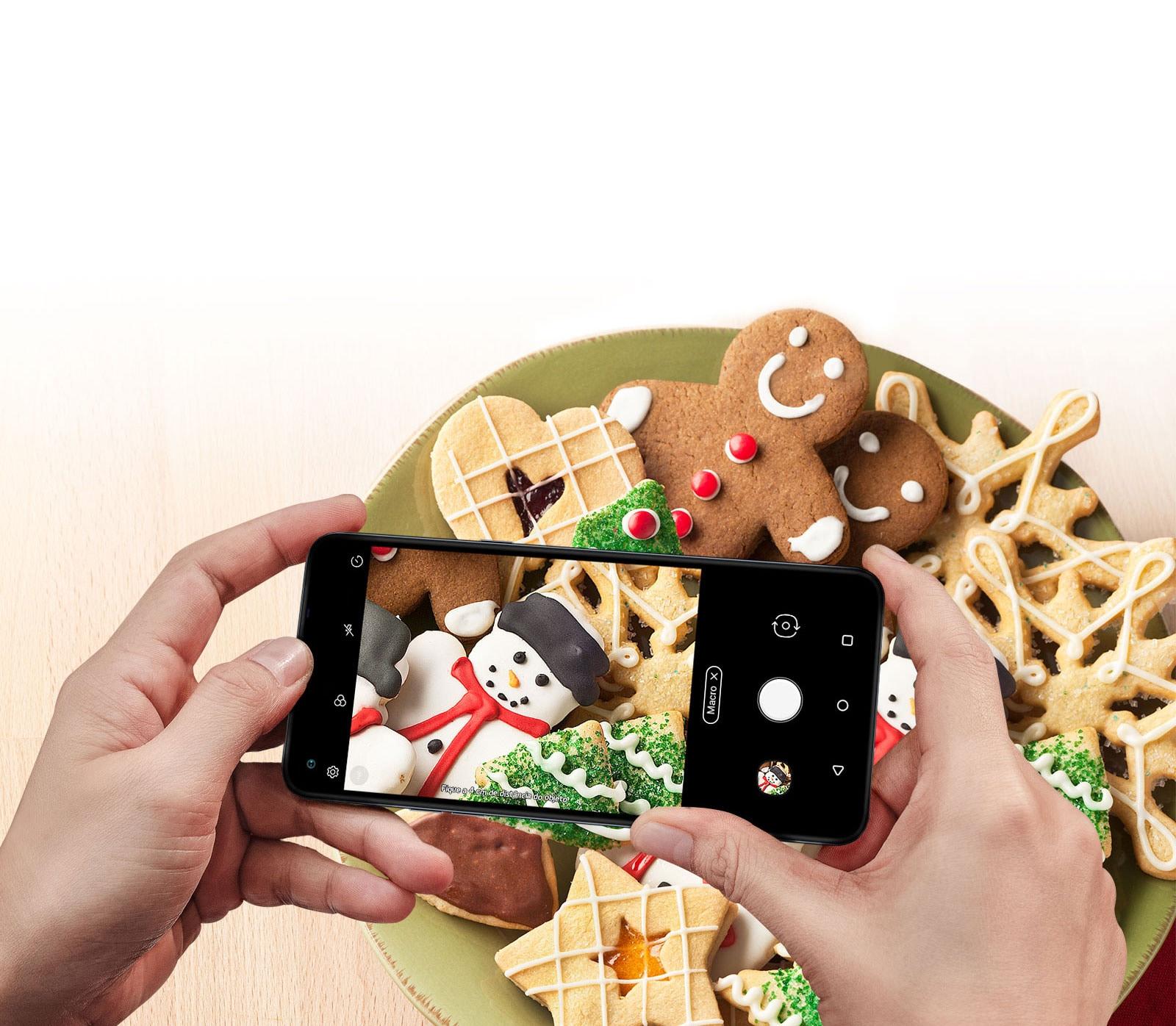 Close de alguém segurando um smartphone e fotografando biscoitos