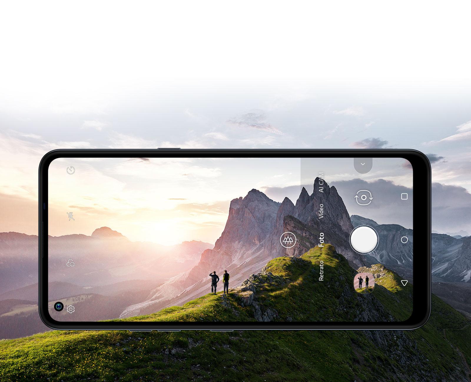 Smartphone fotografando duas pessoas que assistem ao nascer do sol na montanha