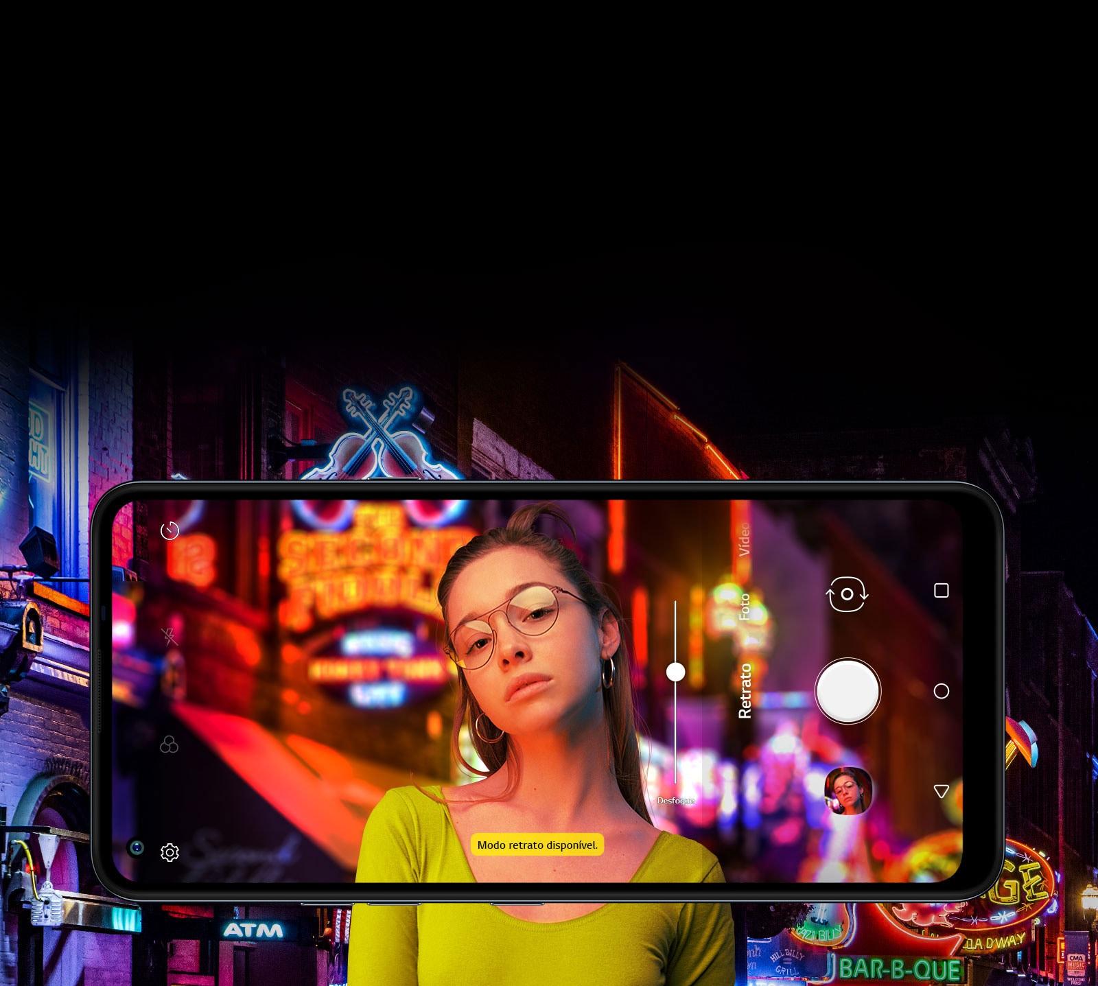 Mulher a tirar selfie tendo ao fundo uma rua repleta de letreiros de neon