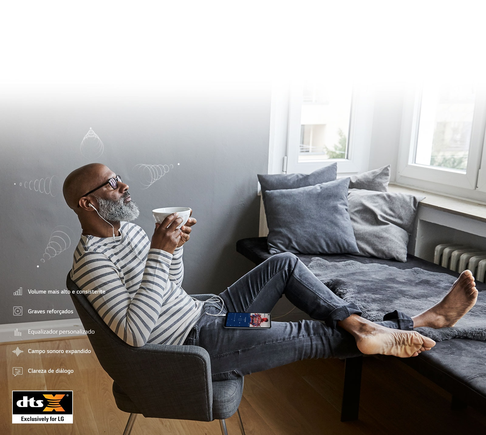 Homem bebendo café e ouvindo música nos fones de ouvido, sentado numa cadeira