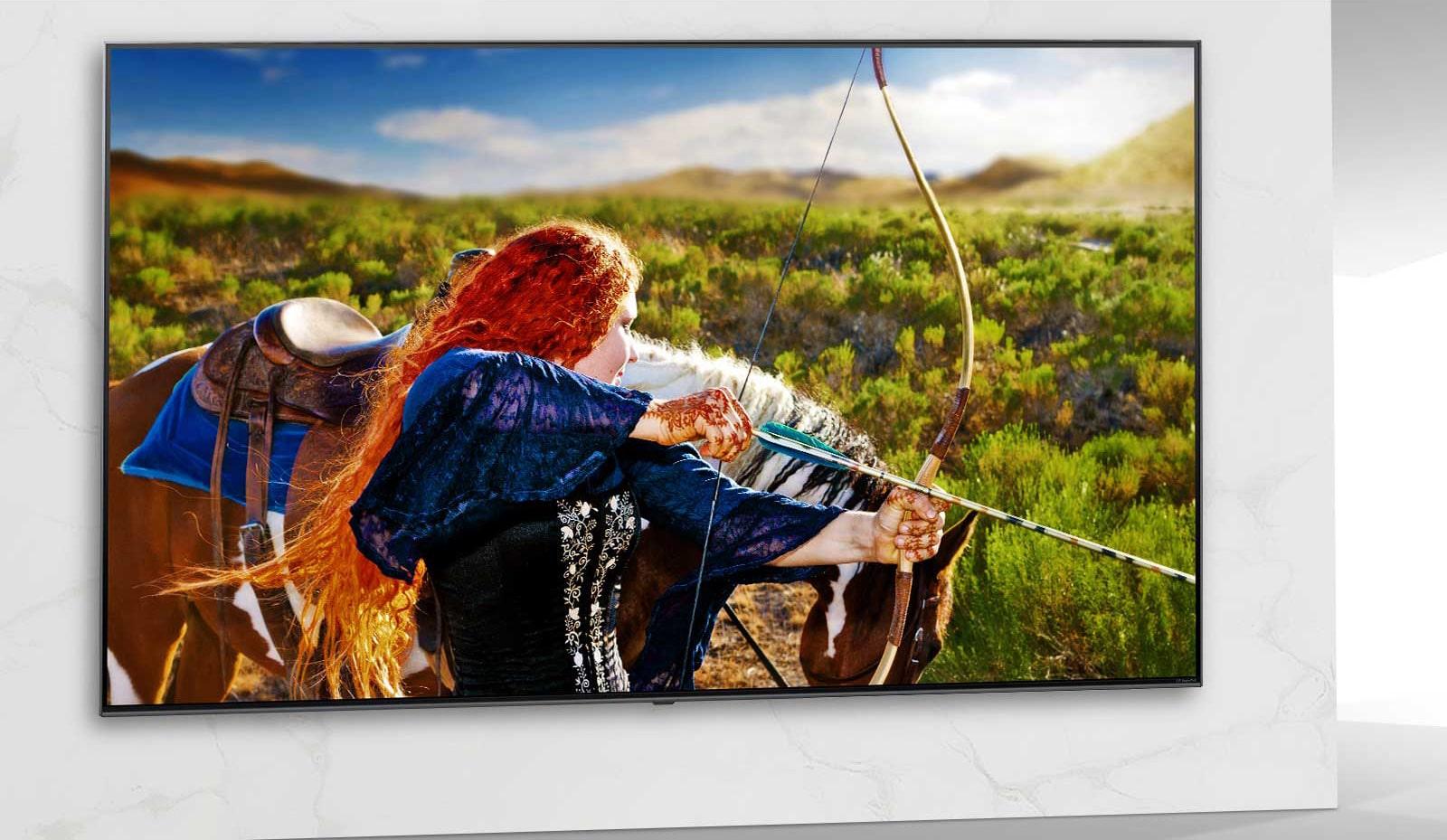 A TV mostra a cena de um filme com uma mulher atirando uma flecha com seu arco