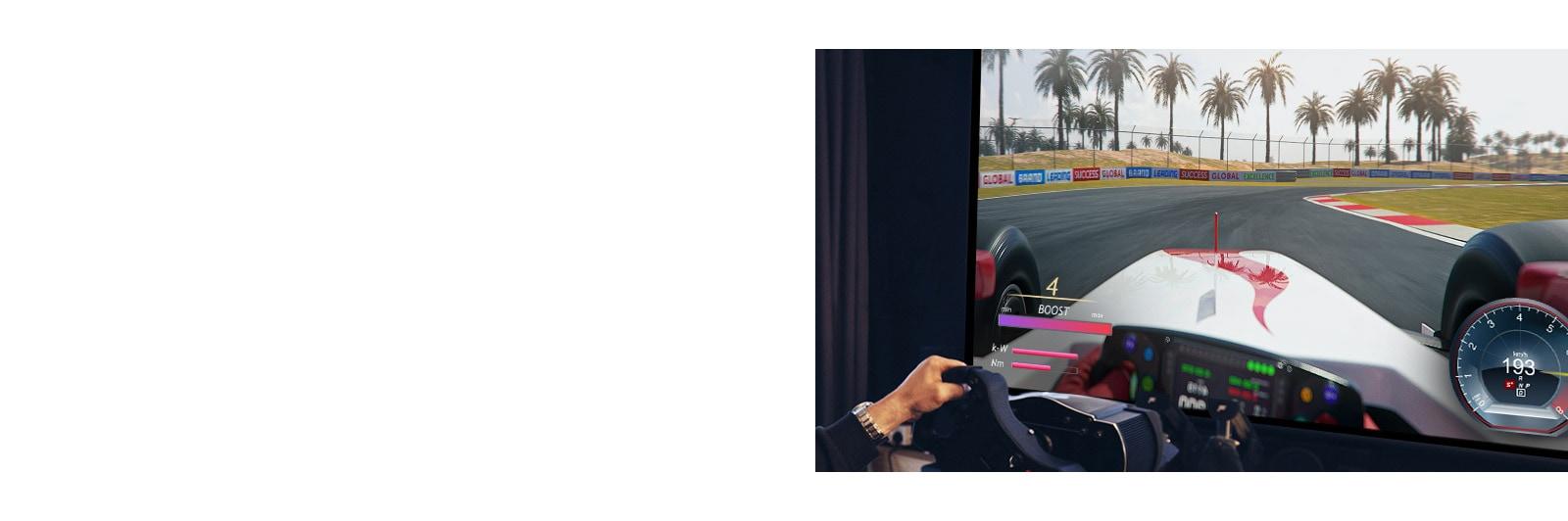 Visão de perto do jogador segurando um volante de corrida e jogando um jogo de corrida na tela da TV.