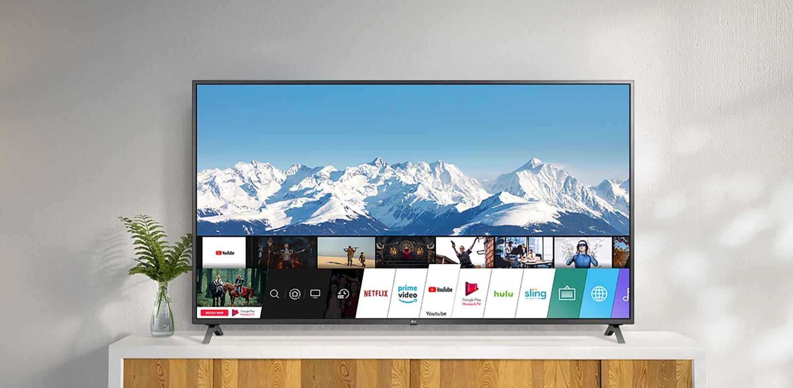 A TV em um suporte branco contra uma parede branca. A tela da TV mostra a tela inicial com o sistema operacional webOS.