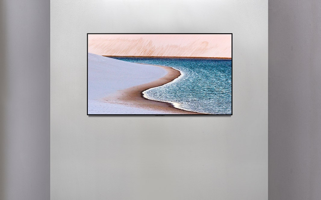 TV on a wall showing an image of the seashore