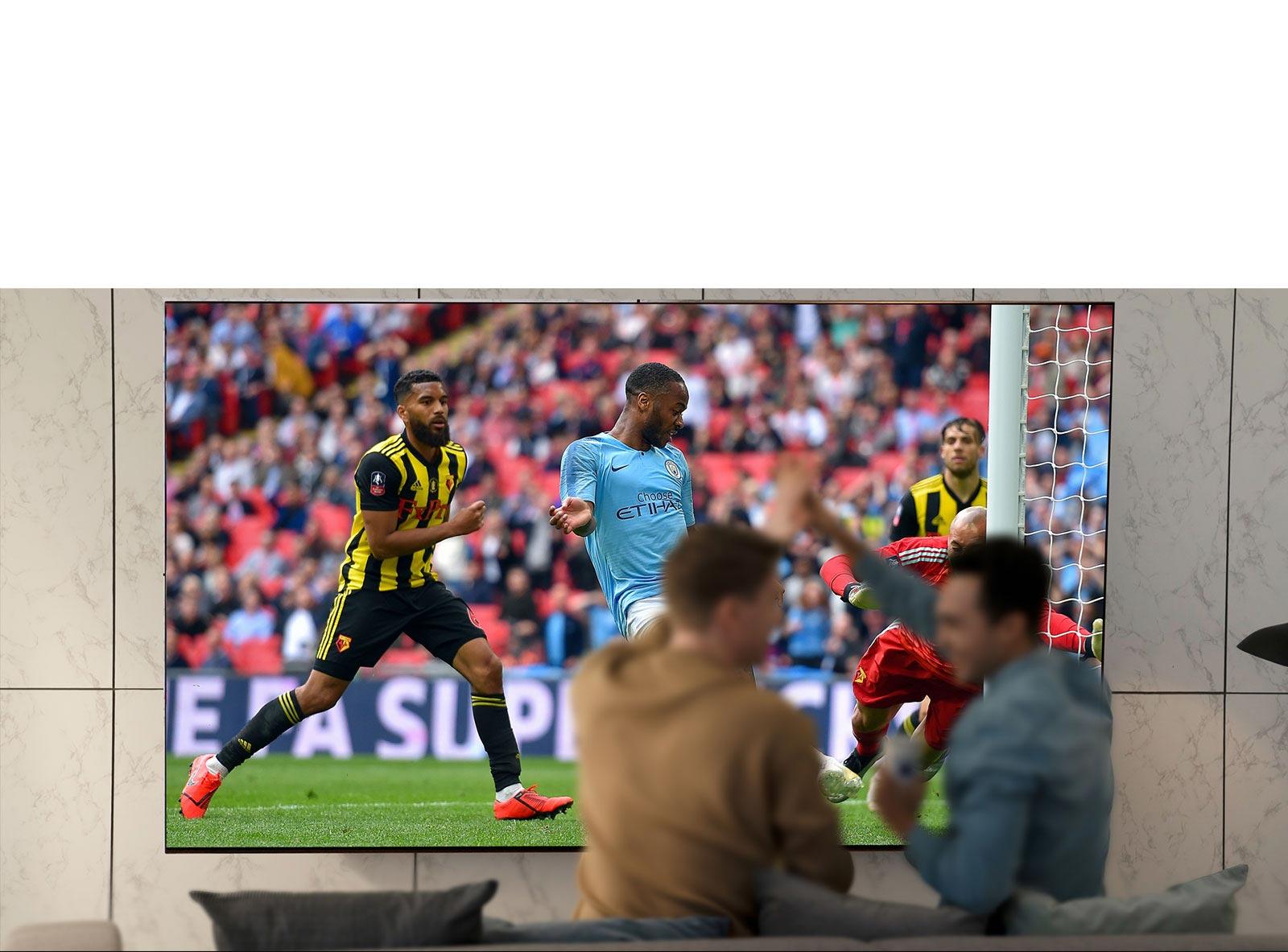 Des gens regardent un match de sport à la télévision dans le salon sur un écran de télévision ultralarge