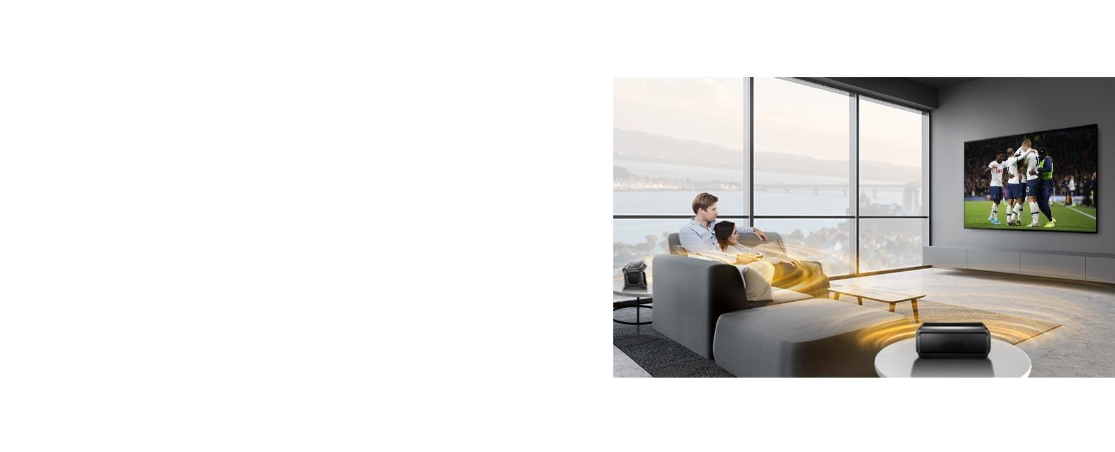 Un homme et une femme regardent un match de sport à la télévision dans le salon avec des haut-parleurs arrière Bluetooth