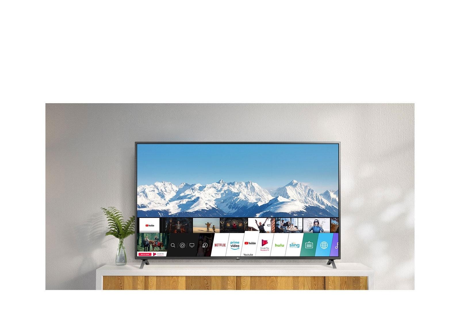 Un téléviseur installé sur un socle blanc contre un mur blanc. L'écran du téléviseur affiche l'écran d'accueil avec webOS.
