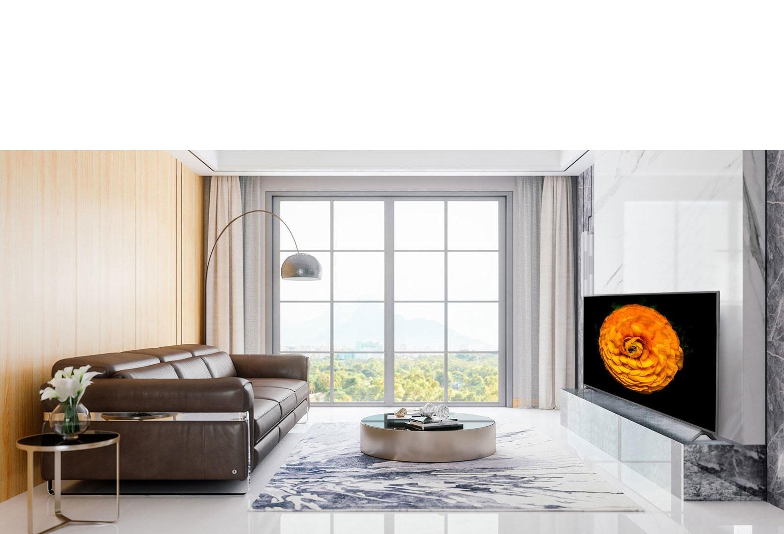Un téléviseur UHD de LG fixé au mur dans un salon au décor minimaliste. L'image d'une fleur est affichée sur l'écran du téléviseur.