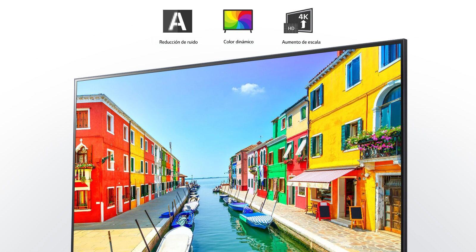 La pantalla de un televisor muestra una ciudad portuaria en la que los edificios están pintados de múltiples colores y los pequeños barcos están anclados en un puerto largo y estrecho.