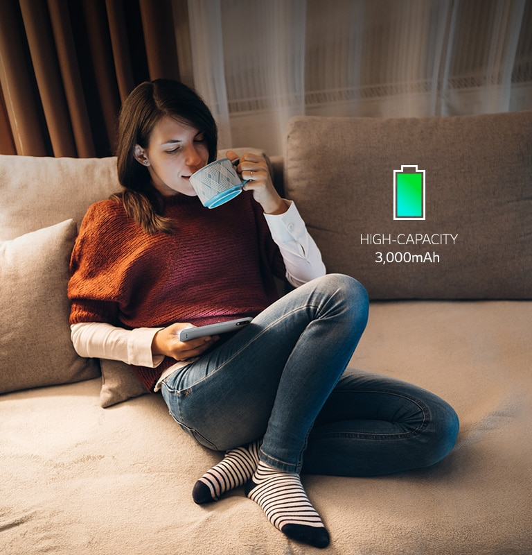 Woman sitting on a sofa drinking coffee and watching her smartphone