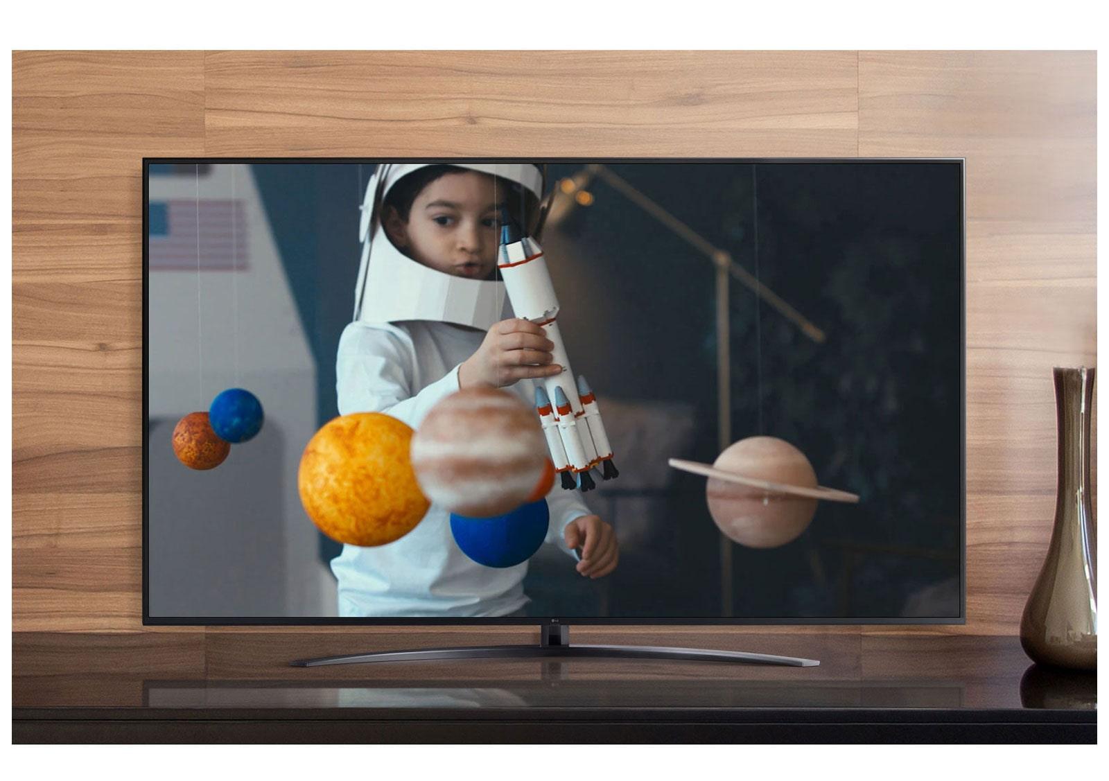 La pantalla de un televisor que reproduce un video de un niño con un traje de astronauta hecho por él, jugando con una nave espacial en su habitación decorada con miniaturas de planetas (reproducir el video)