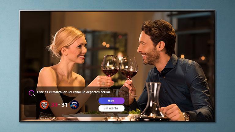 Un hombre y una mujer chocando vasos en una pantalla de televisor, mientras se notifican las alertas deportivas