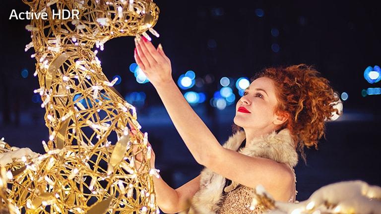 Esta tarjeta describe el HDR activo. Es una imagen cinematográfica de una mujer tocando una escultura brillante.