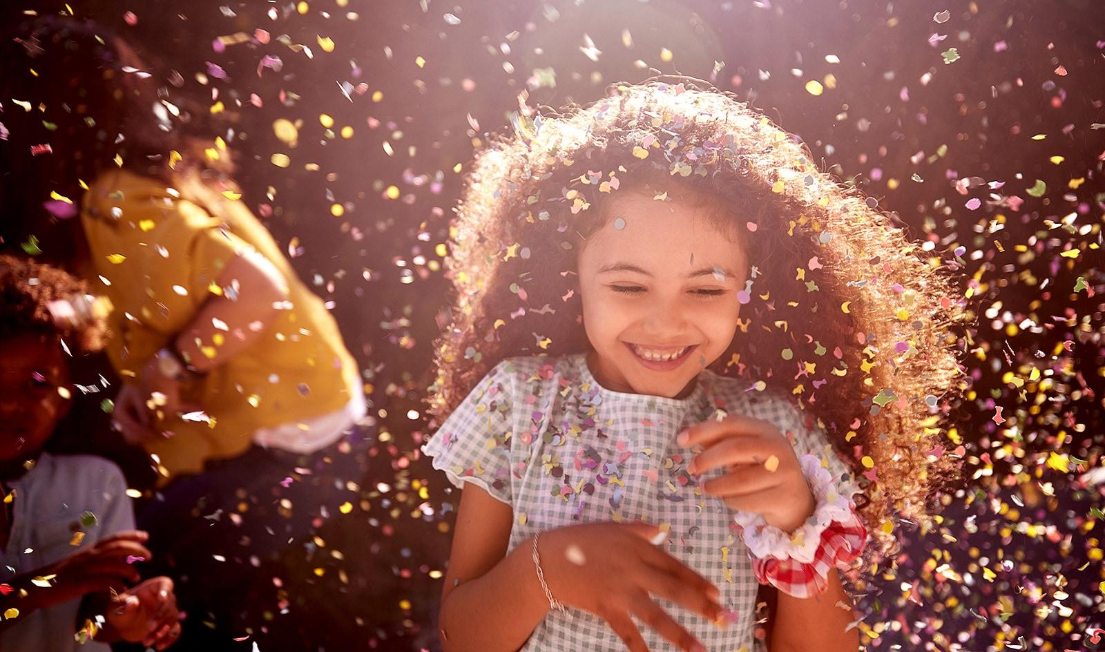 Esta tarjeta describe la calidad del sonido. Es una imagen de una niña sonriendo alegremente en celebración.