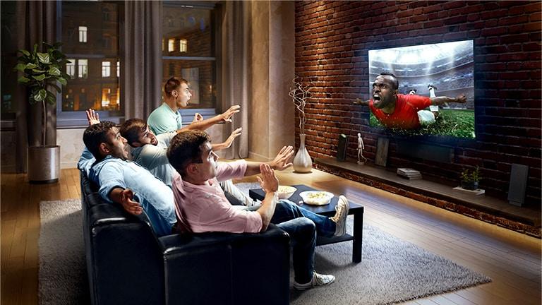 Esta tarjeta describe el virtual surround plus. Una familia sentada en un sofá viendo fútbol en la televisión.
