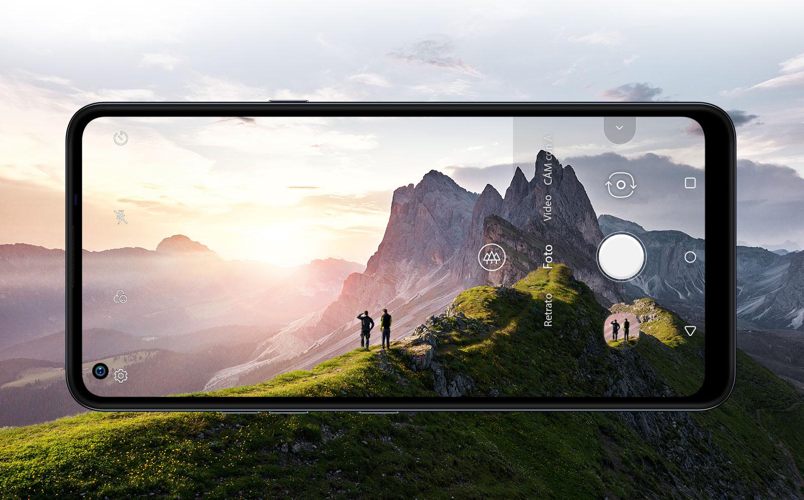Celular fotografiando a dos personas que miran el amanecer en la montaña