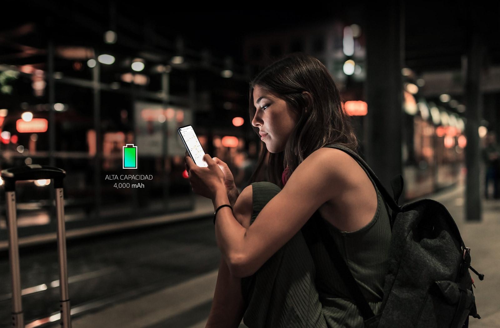 Mujer que navega por internet en su teléfono inteligente tarde en la noche en la estación de metro con suficiente batería