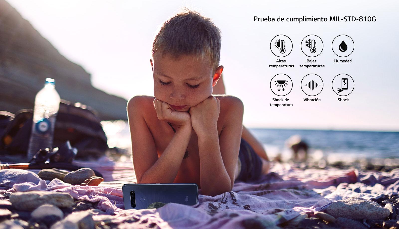 Niño acostado en la playa mientras mira una película en su teléfono inteligente