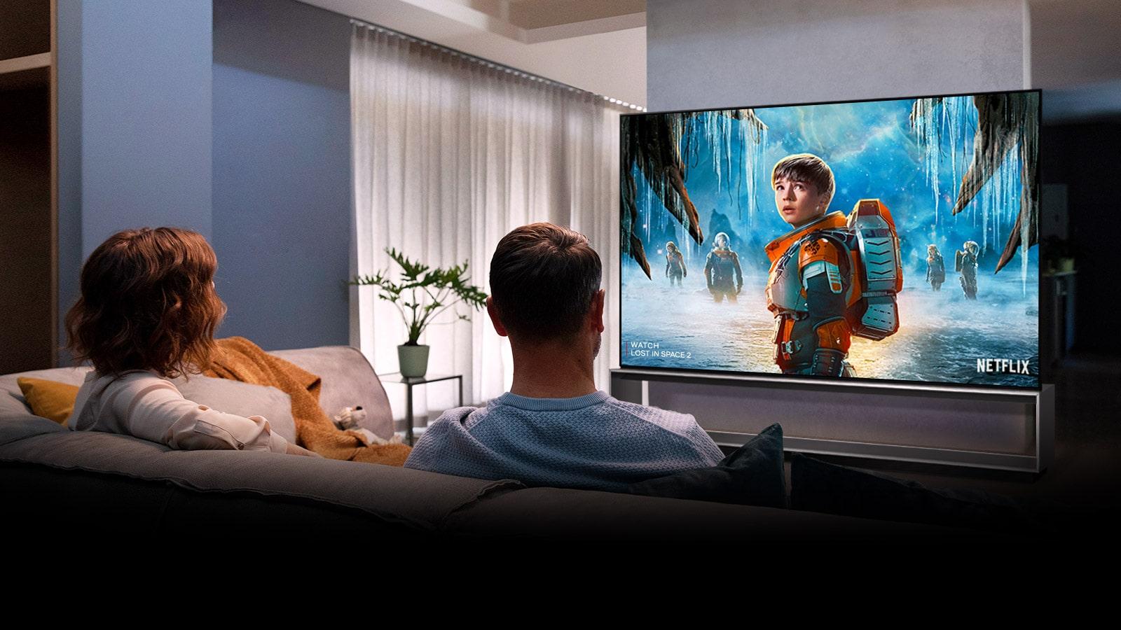 Pár sedící na pohovce v obývacím pokoji a sledující seriál LOST IN SPACE 2 v televizi
