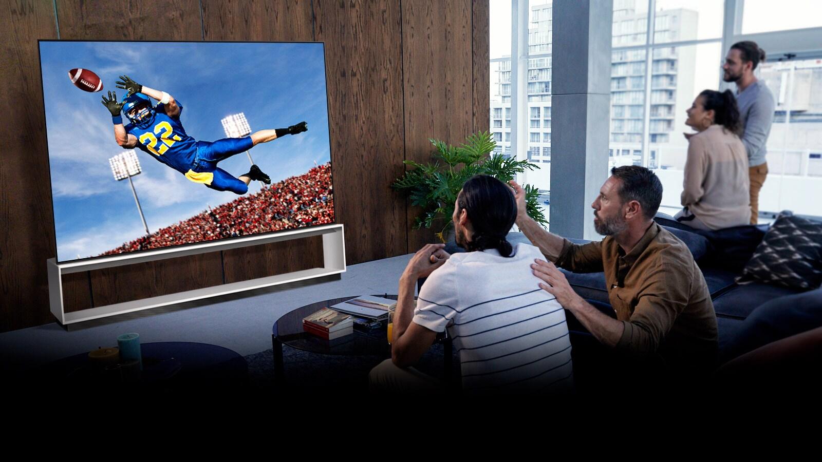 Lidé sledují americký fotbal v televizi v obývacím pokoji