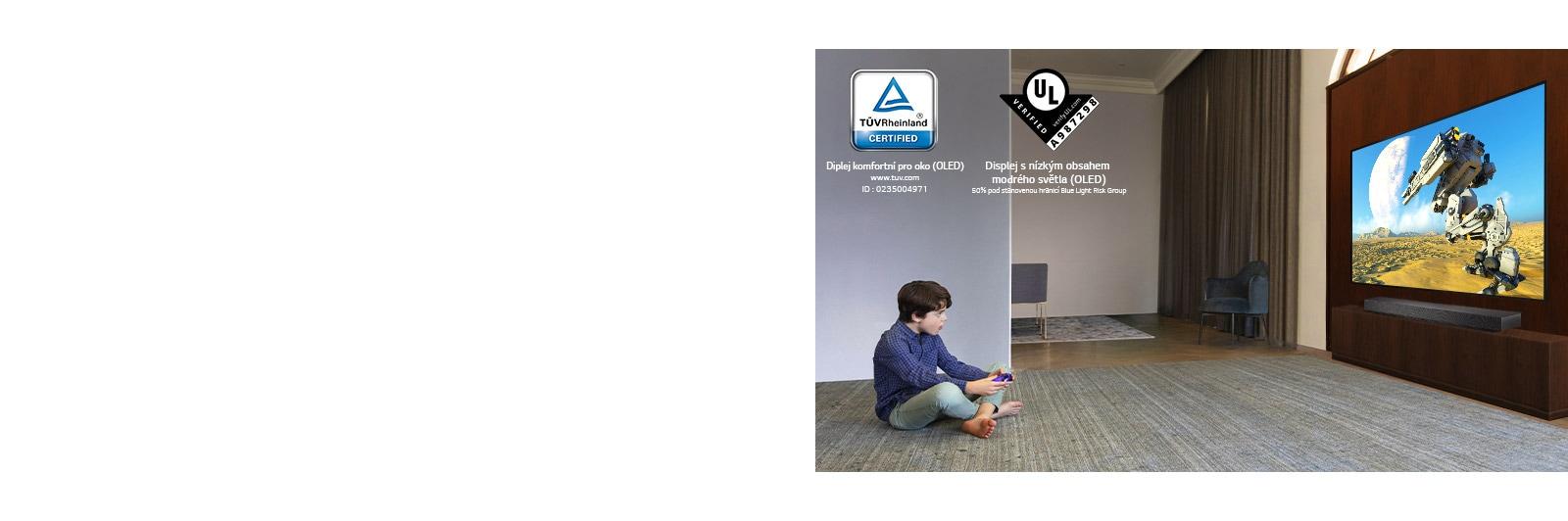Dítě sedící na podlaze, které drží joystick ahraje hru na TV obrazovce
