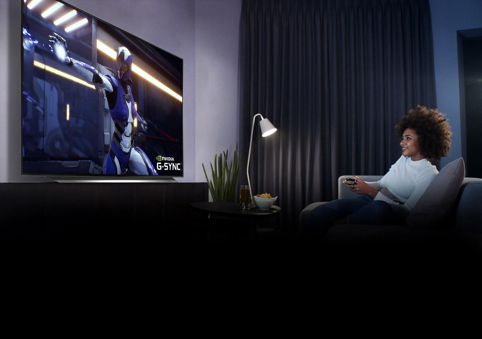 Žena sedí na pohovce, drží joystick při hraní her na televizní obrazovce