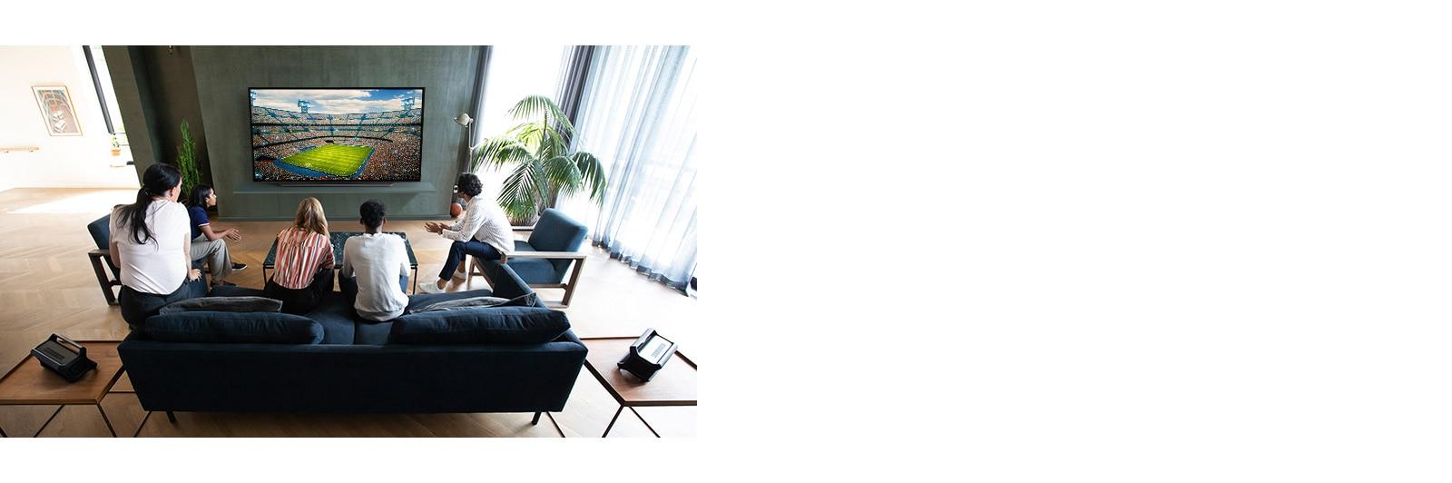 Lidé sledující sportovní zápas na televizoru vobývacím pokoji se zadními reproduktory Bluetooth