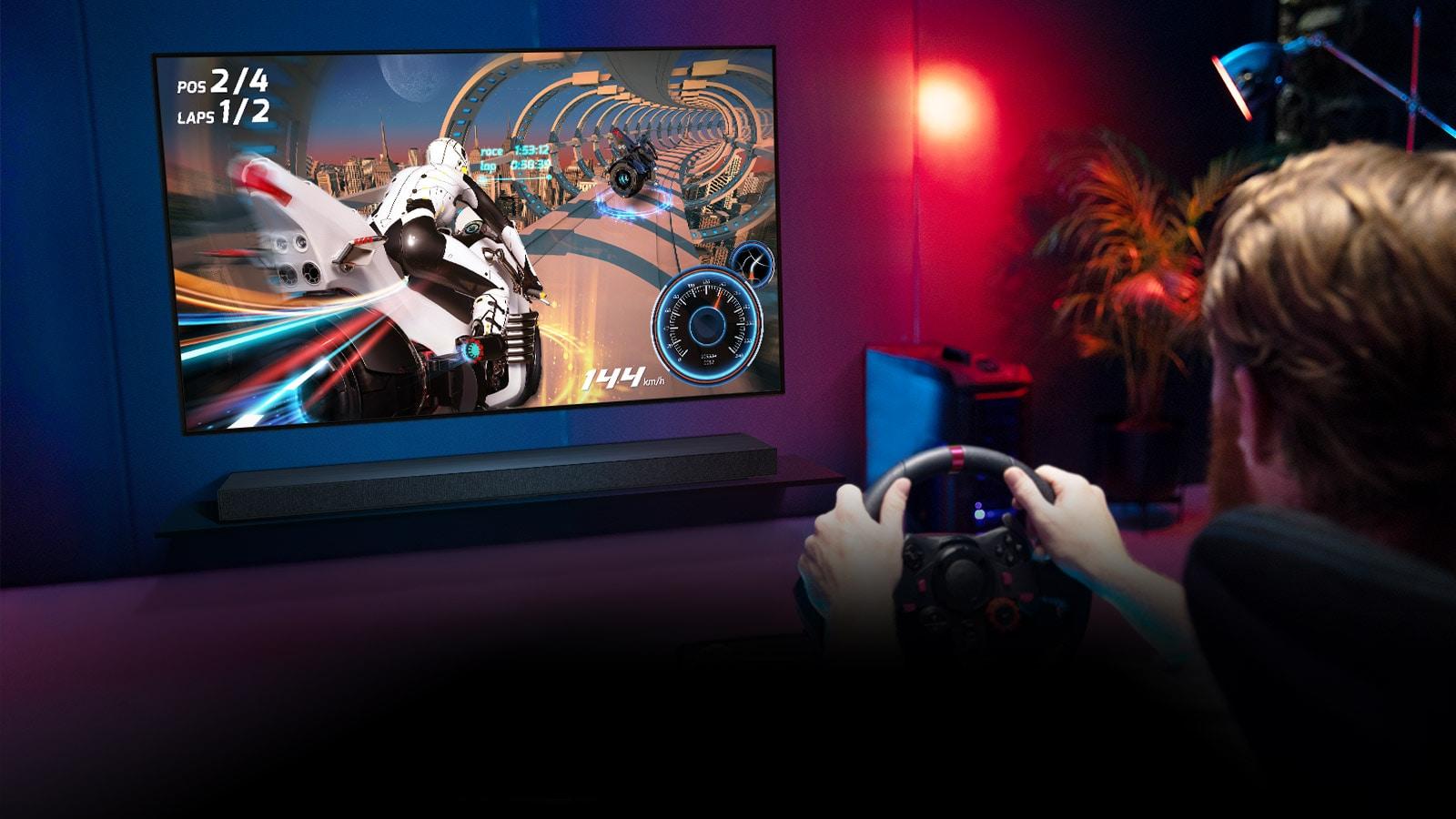 Muž, který sedí vherním křesle, drží herní volant ahraje závodní hru na televizní obrazovce