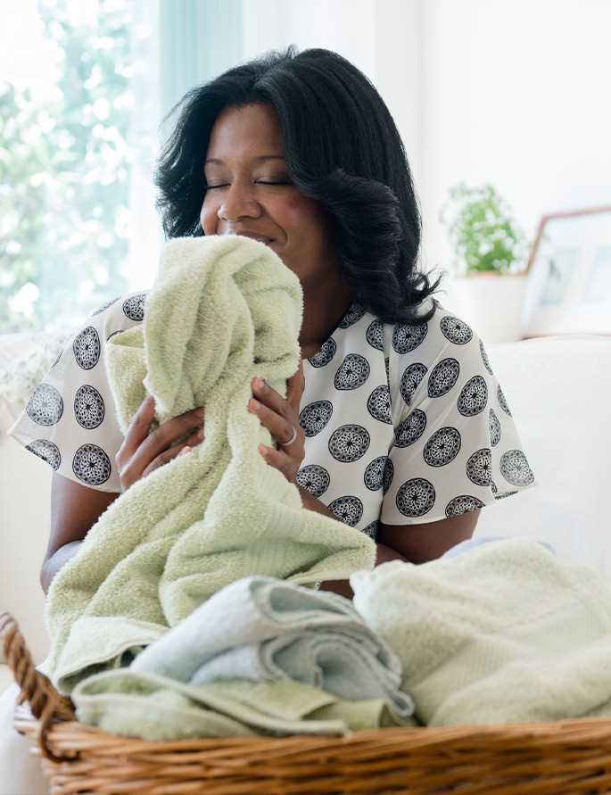 An image of a woman smelling her freshly washed towel.