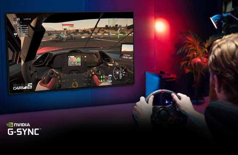 Un uomo seduto su una sedia da gioco con le mani attorno al volante di un gioco di corse mentre si gioca a un gioco di corse in TV