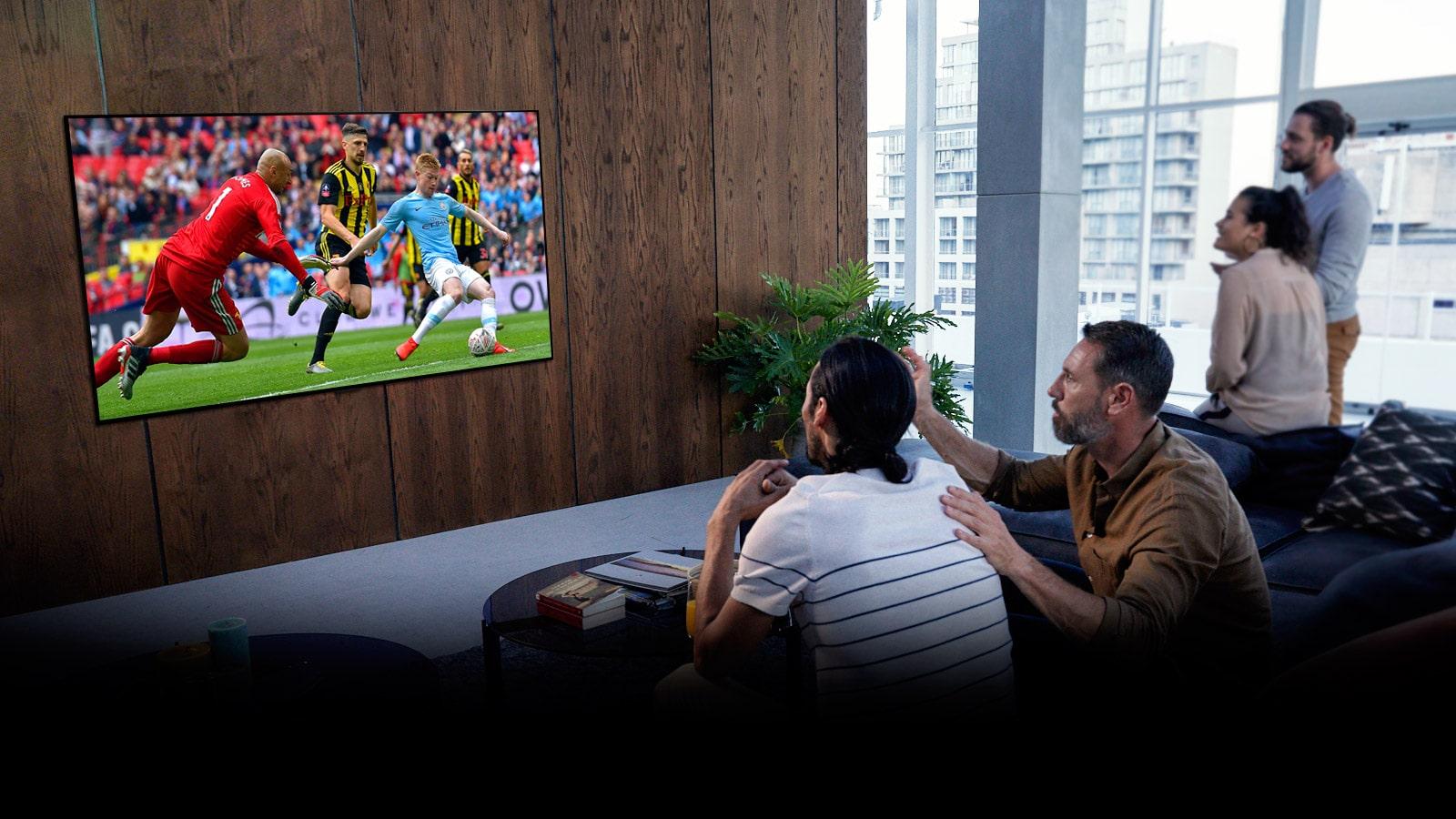 """Persone che guardano una partita di """"Tottenham"""" in TV nel loro salotto"""