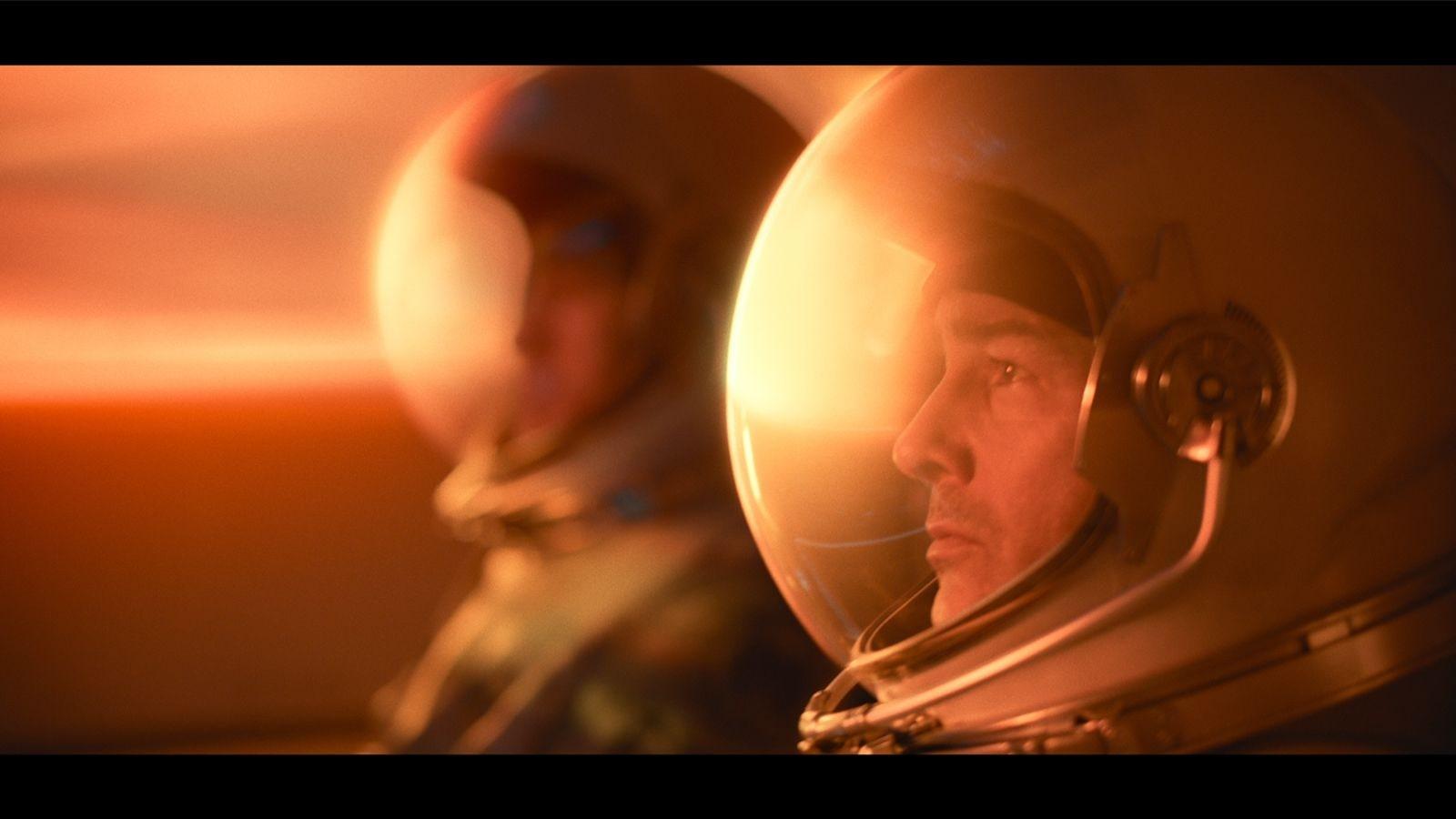 """Moški gleda """"The Midnight Sky"""" v domačem kinu na Netflixu.  In slogan """"Bodi junak"""" je viden"""