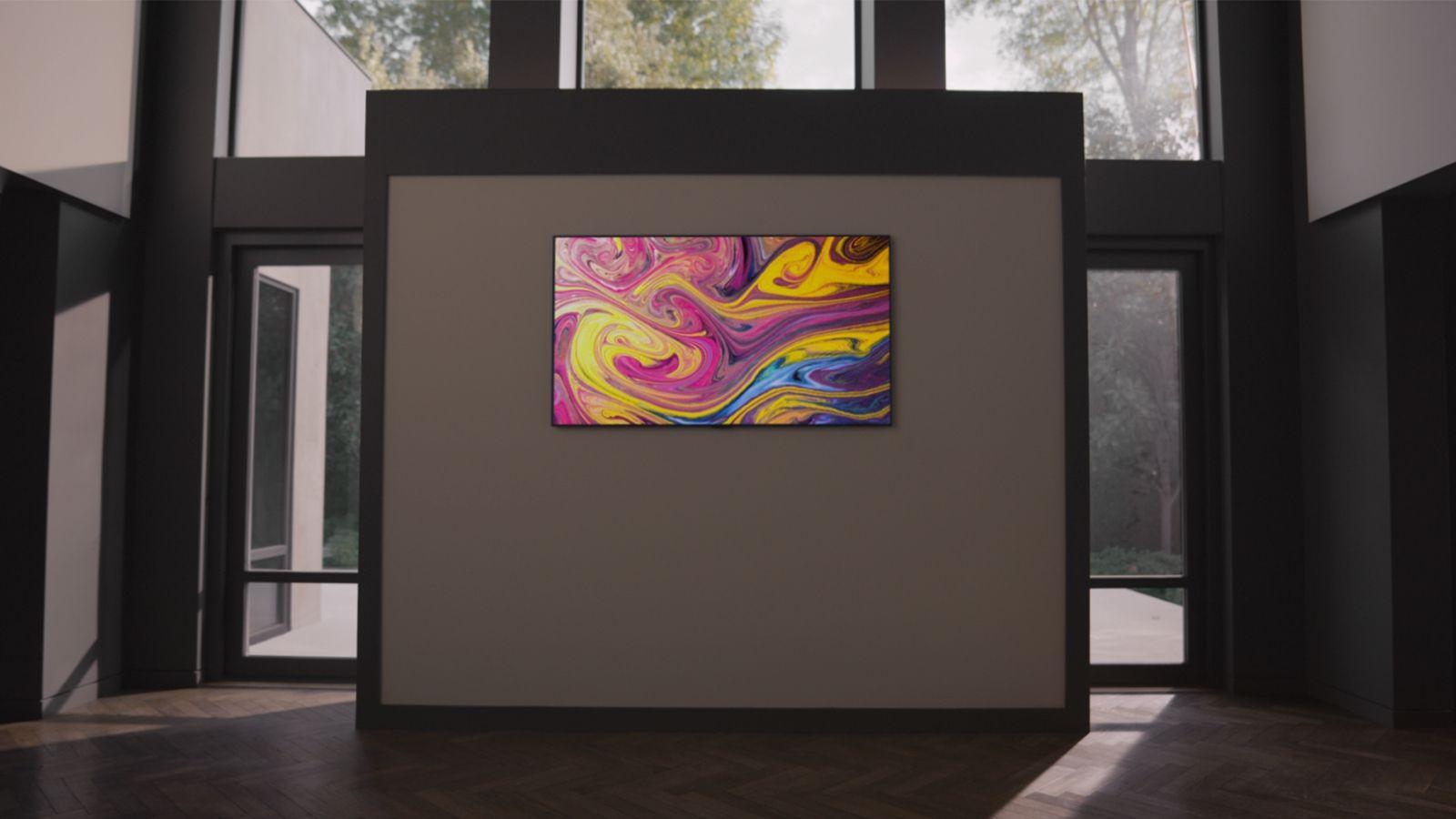 """Eine Frau, die in einer galerieähnlichen Wohnung einen Gallery TV an der Wand hängen hat, betrachtet interessiert den Gallery-TV-Standfuß. Außerdem ist der Slogan """"Complete your space, Light the space up"""" zu sehen."""