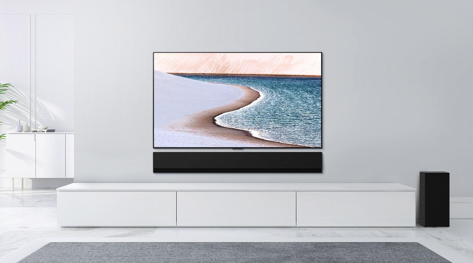 Ein Fernseher ist an einer hellgrauen Wand befestigt. Darunter befindet sich die LG Soundbar auf einer weißen Kommode. Auf dem Fernseher ist ein Strand zu sehen.