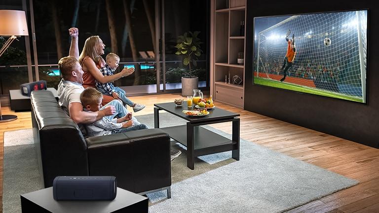 Družina sedi na kavču in po televiziji gleda nogometno tekmo.